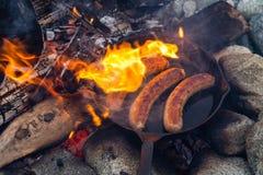 Kochen von Würsten in der Roheisenbratpfanne auf Lagerfeuer beim Kampieren Gutes und positives Lagerfeuerlebensmittel Lizenzfreie Stockbilder