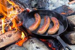 Kochen von Würsten in der Roheisenbratpfanne auf Lagerfeuer beim Kampieren Gutes und positives Lagerfeuerlebensmittel Lizenzfreie Stockfotografie