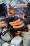 Kochen von Würsten in der Roheisenbratpfanne auf Lagerfeuer beim Kampieren Gutes und positives Lagerfeuerlebensmittel Stockfotografie