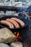 Kochen von Würsten in der Roheisenbratpfanne auf Lagerfeuer beim Kampieren Gutes und positives Lagerfeuerlebensmittel Stockfotos