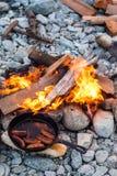 Kochen von Würsten in der Roheisenbratpfanne auf Lagerfeuer beim Kampieren Gutes und positives Lagerfeuerlebensmittel Lizenzfreies Stockfoto