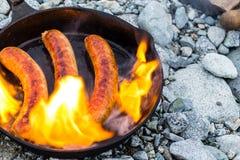 Kochen von Würsten in der Roheisenbratpfanne auf Lagerfeuer beim Kampieren Gutes und positives Lagerfeuerlebensmittel Stockfoto