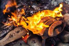 Kochen von Würsten in der Roheisenbratpfanne auf Lagerfeuer beim Kampieren Gutes und positives Lagerfeuerlebensmittel Stockbild