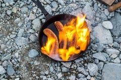 Kochen von Würsten in der Roheisenbratpfanne auf Lagerfeuer beim Kampieren Gutes und positives Lagerfeuerlebensmittel Stockbilder