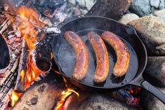 Kochen von Würsten in der Roheisenbratpfanne auf Lagerfeuer beim Kampieren Gutes und positives Lagerfeuerlebensmittel Lizenzfreies Stockbild
