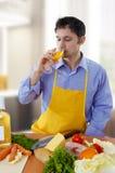Kochender und trinkender weißer Wein des Mannes Stockfotografie