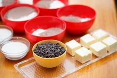 Kochensatz bunte Schüsseln mit Schokoladenplätzchen, Mehl, Kakaopulver, Zucker und Blöcke von Butter stehen an hellbraunem hölzer Stockfotos