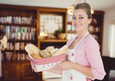 Kochfrau mit Brot aalen sich im Wohnzimmer Lizenzfreies Stockfoto