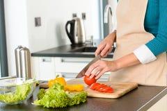 Kochfrauenausschnitttomatesalat-Messerküche Stockbild