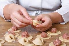 Kochhände sculpt Mehlklöße mit Hackfleisch stockfoto