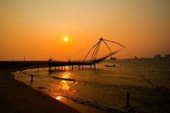 Kochi chinese fishnets and the boat with fishermen on sunset Stock Photo