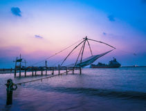Kochi chinese fishnets and vessel on sunset  in Kerala. Royalty Free Stock Images
