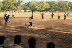 Cricket game. Sports in Kochi, India. Kochi, India - November 29, 2015: Indian men playing cricket on a field on a sunny day. Competition. Spectators. Since royalty free stock photo