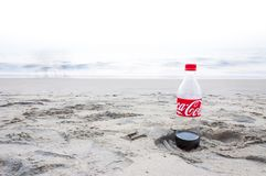 Coca Cola bottle left on a footprint in the sand. Kochi, Kerala, India - January 11, 2015: Almost empty plastic Coca Cola bottle left on a footprint in the sand stock photography