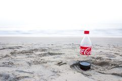 Coca Cola bottle left on a footprint in the sand. Kochi, Kerala, India - January 11, 2015: Almost empty plastic Coca Cola bottle left on a footprint in the sand stock image