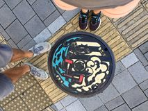 Top view of male and female legs standing in front of a Japanese manhole stock images