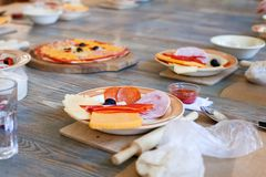 Kochkurs, kulinarisch Lebensmittel- und Leutekonzept, Desktop, der zur Arbeit, Bestandteile für italienische Pizza fertig wird Stockfotos