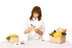 Kochmädchen bildet das Schnitzen einer Mangofrucht Lizenzfreie Stockfotografie