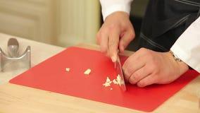 Kock Chopping Garlic på skärbrädan med a arkivfilmer