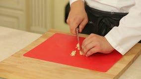 Kock Chopping Garlic på skärbrädan med en kniv stock video