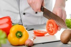 Kock Cutting en tomat arkivfoton