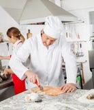 Kock Cutting Ravioli Pasta med kollegaarbete arkivfoton
