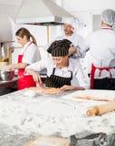 Kock Cutting Ravioli Pasta med kollegor in arkivfoto