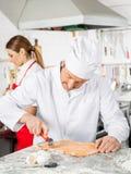 Kock Cutting Ravioli Pasta på räknaren i kök arkivfoto