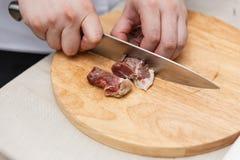 Kock Cutting Raw Meat på träsnittet royaltyfri bild