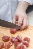 Kock Cutting Raw Meat på träsnittet royaltyfri foto