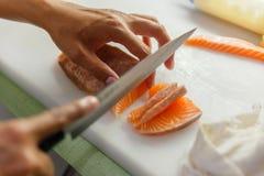 Kock Cutting Salmon för framställning av sashimien royaltyfria foton