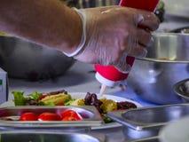 Kock Drizzling en sås från en röd flaska på en förberedd maträtt med rostfria bunkar omkring under att laga mat mästarklass, semi arkivbilder
