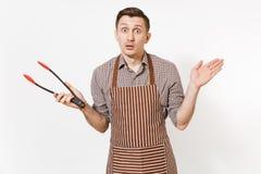 Kock för ung man i det randiga bruna förklädet, skjorta som rymmer svart kök som tjänar som plast- par av tång för sallad som iso royaltyfri bild