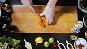 Kock Hands Cutting Carrot på träbräde stock video