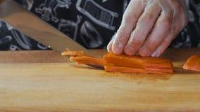 Kock Hands Cutting And som hugger av moroten vid kniven stock video
