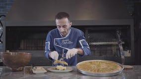 Kock i blå likformig och vita latexhandskar som förbereder sig för att tjäna som den östliga söta kunafaen som inom sätter ost av lager videofilmer