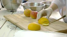 Kock i handskar som skivar citronen stock video