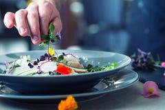 Kock i hotell- eller restaurangkökmatlagning, endast händer Han arbetar på mikroörtgarneringen förbereda salladgrönsaken royaltyfria bilder