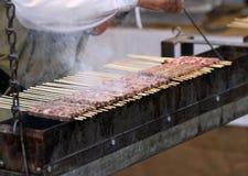 Kock i medeltida dräkt, medan laga mat kött Arkivbilder