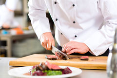 Kock i restaurangkök som förbereder mat Royaltyfri Bild