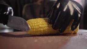 Kock i svarta spishandskar som klipper och skivar fruktsaftmajs för att grilla på träskrivbordet close upp lager videofilmer