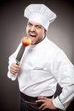 Kock med äpplet på kniven royaltyfri bild
