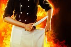 Kock med kniven, främre sikt med brand på bakgrund tolkning 3D och foto Hög upplösning royaltyfria foton