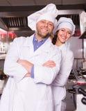 Kock och hans hjälpreda på bistrokök arkivfoto