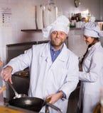 Kock och hans hjälpreda på bistrokök royaltyfri bild