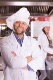 Kock och hans hjälpreda på bistrokök arkivbild