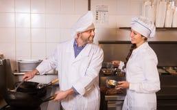 Kock och hans hjälpreda på bistrokök royaltyfria foton