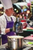 Kock på arbete på matfestivalen i Utrecht i Nederländerna Fotografering för Bildbyråer