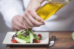 Kock Pouring Olive Oil Over Salad fotografering för bildbyråer
