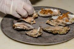 Kock Preparing Cajun Oysters på den halva Shell Royaltyfri Fotografi